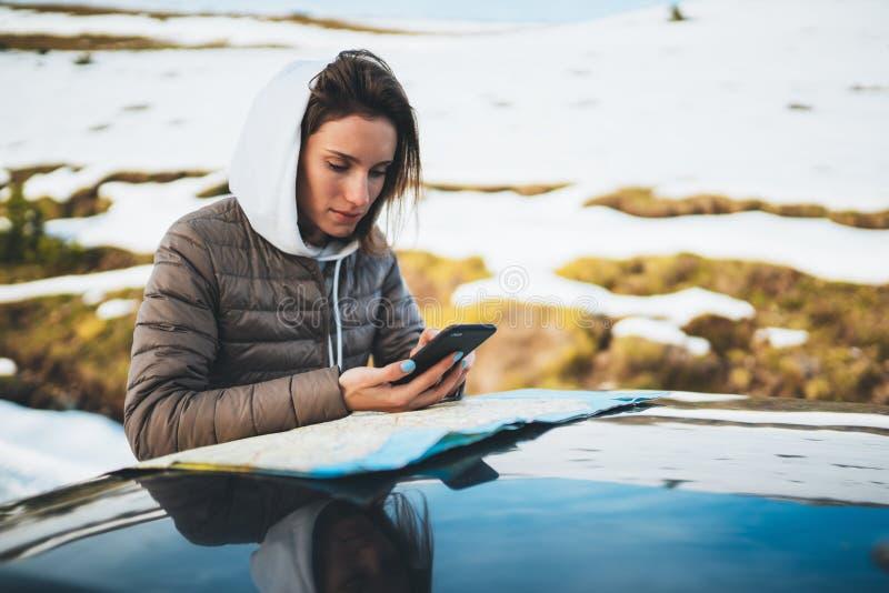 El control de la muchacha en teléfono móvil de las manos y la mirada en el mapa, inconformista disfrutan de la naturaleza del inv imagen de archivo