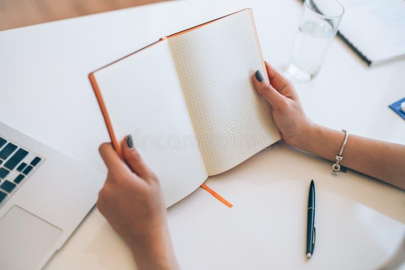 El control de las manos de la mujer abre el cuaderno en blanco en fondo de los materiales de oficina fotografía de archivo