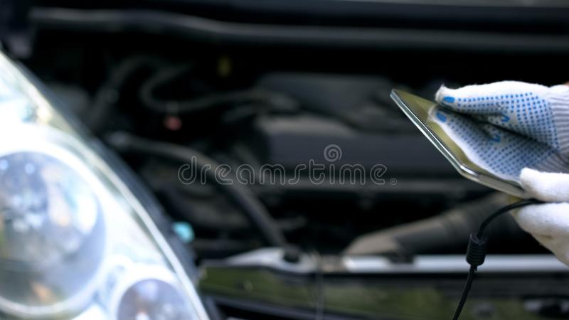 El controlar de motor de coche con la tableta, ingeniero utiliza las informáticas para la reparación imagen de archivo libre de regalías