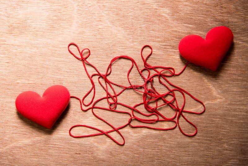 El corazón de dos rojos y la secuencia roja compleja conectan juntos en los vagos de madera imagenes de archivo