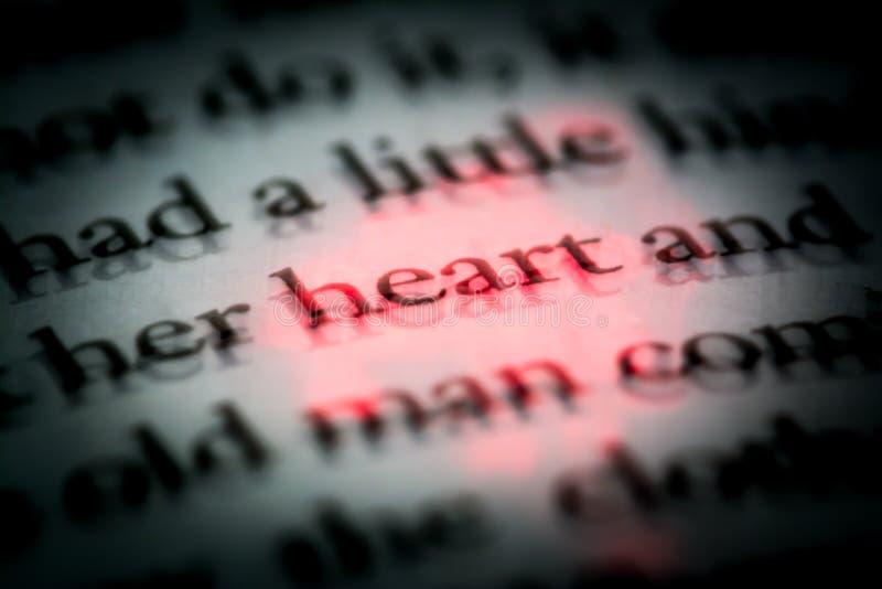 El corazón de la palabra en un libro en cierre inglés para arriba, macro, destacado en rojo El texto en el libro con el efecto 3D fotografía de archivo libre de regalías
