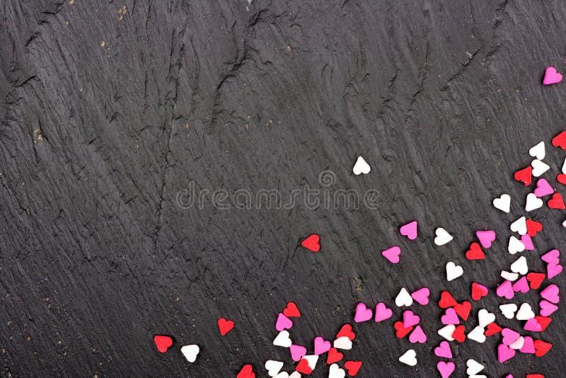 El corazón del caramelo de día de San Valentín asperja la frontera de la esquina sobre un fondo negro foto de archivo
