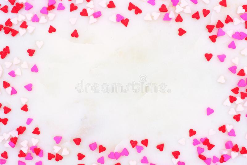 El corazón del caramelo de día de San Valentín asperja el marco sobre un fondo texturizado blanco fotos de archivo