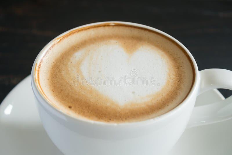 El corazón forma arte del Latte de la leche de la espuma en enfoque de la taza del café con leche imagen de archivo