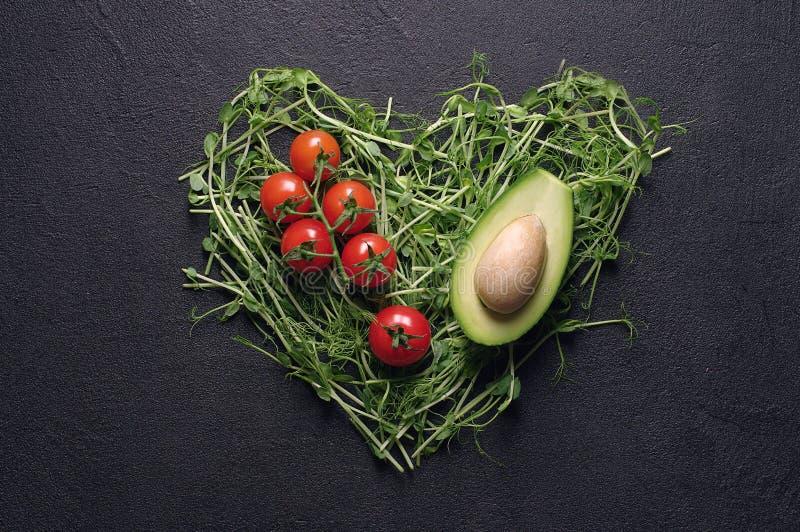 El corazón hizo de lanzamientos del guisante, del aguacate y de los tomates de cereza jovenes en fondo negro; Visión superior, en foto de archivo libre de regalías