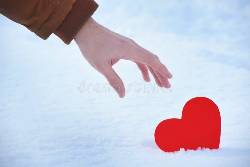 El corazón rojo perdido es solo en un día de tarjetas del día de San Valentín, corazón en una nieve fría del invierno, con una lu fotos de archivo