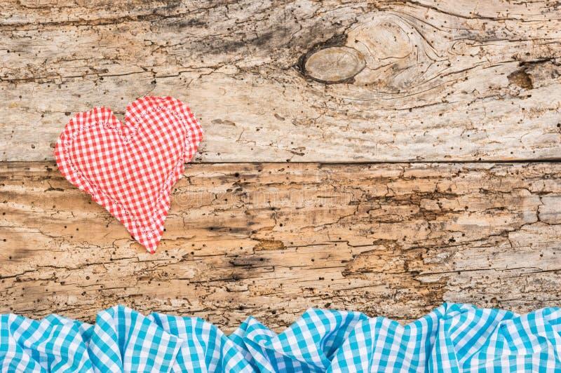 El corazón rojo rústico del amor en viejo fondo de madera con el azul comprobó el marco imagenes de archivo