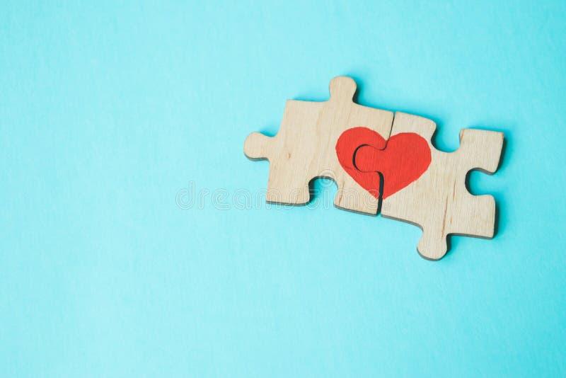 El corazón rojo se dibuja en los pedazos del rompecabezas de madera que miente uno al lado del otro en fondo azul Concepto del am imagenes de archivo