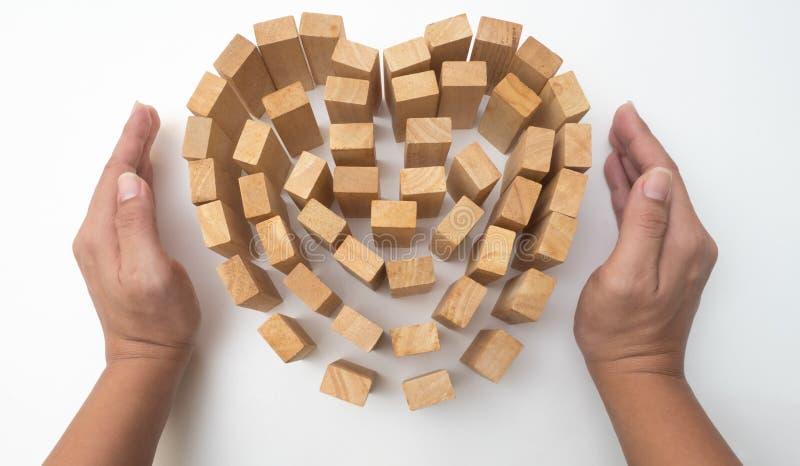 El corazón y la mano de madera del bloque llevan a cabo la protección del concepto su amor encendido imagen de archivo