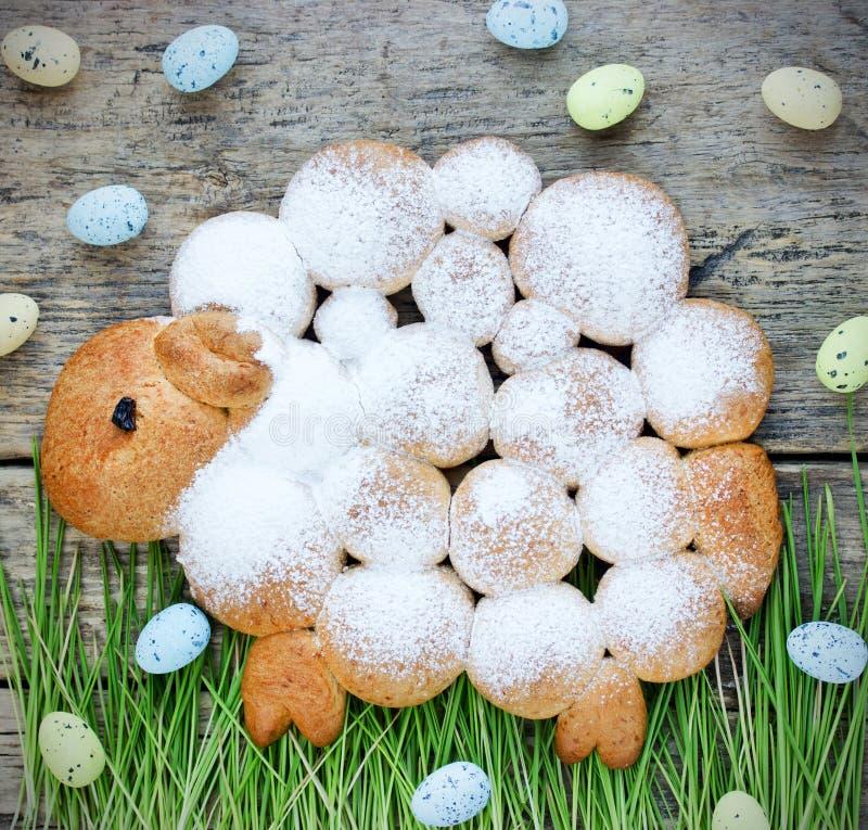 El cordero o las ovejas de Pascua se apelmaza con el azúcar en polvo en ingenio de la hierba verde fotografía de archivo