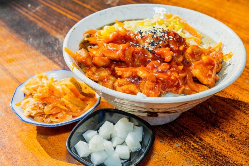 El coreano sofrió el arroz del pollo en el cuenco blanco en la tabla de madera imágenes de archivo libres de regalías