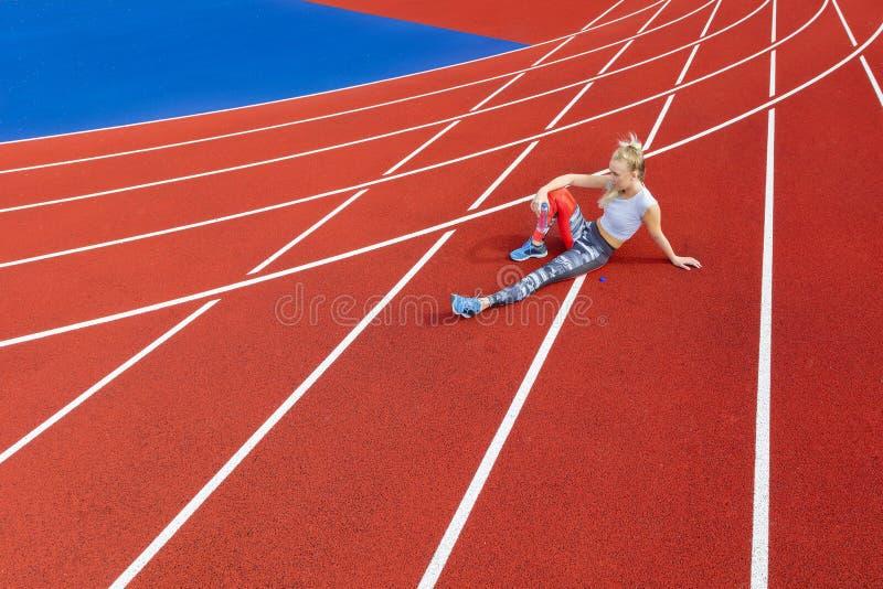 El corredor femenino atlético descansa sobre pista corriente en la arena deportiva fotografía de archivo