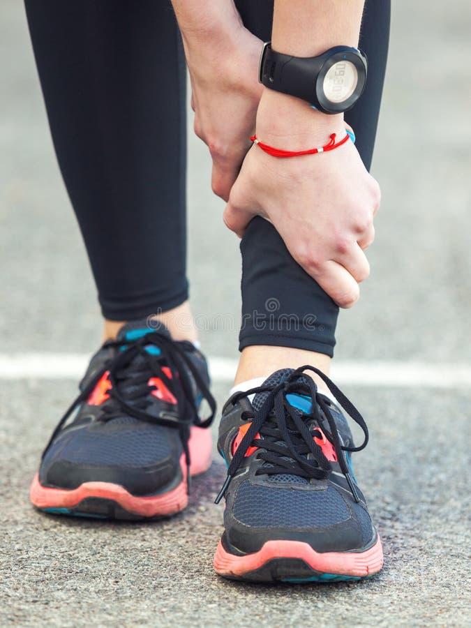 El corredor femenino está llevando a cabo su pierna herida fotos de archivo libres de regalías