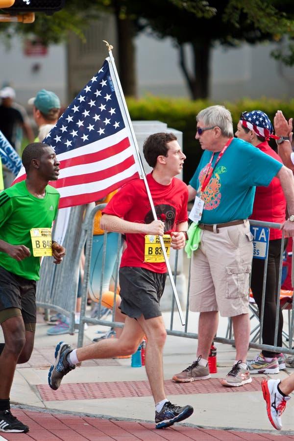 El corredor lleva la bandera americana en el ciclismo en ruta de Atlanta del 4 de julio fotos de archivo libres de regalías