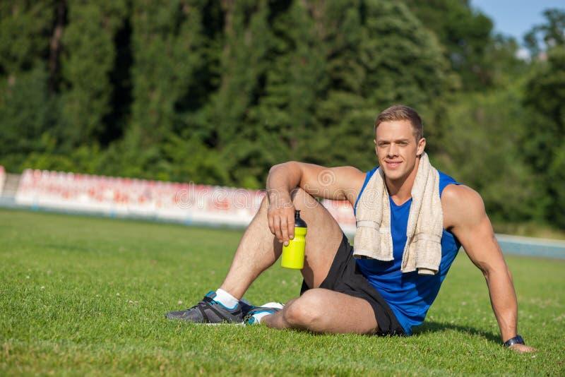 El corredor masculino joven alegre está descansando sobre hierba imagen de archivo libre de regalías