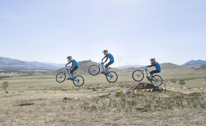 El corredor no identificado supera el salto en la competencia para el ' Taza de Buriatia en una bici de montaña imagen de archivo libre de regalías