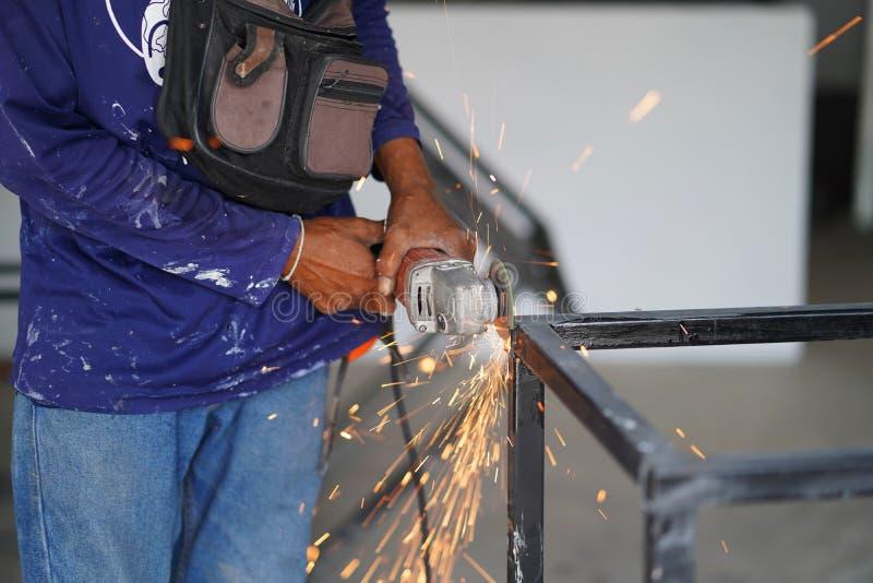 El corte de acero de la amoladora del uso del trabajador crea la tabla del acero del metal Técnico industrial imagen de archivo libre de regalías