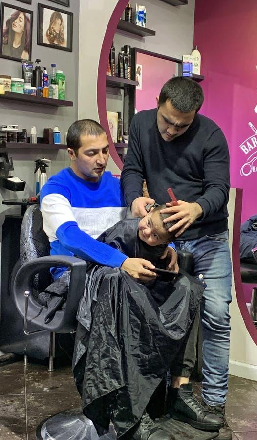 El corte de pelo del niño del problema en rodillas engendra el barbeshop imagenes de archivo