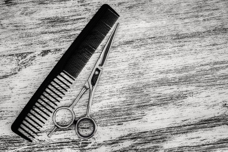 El corte del pelo scissor para los peluqueros y el peine en salón de belleza imagenes de archivo