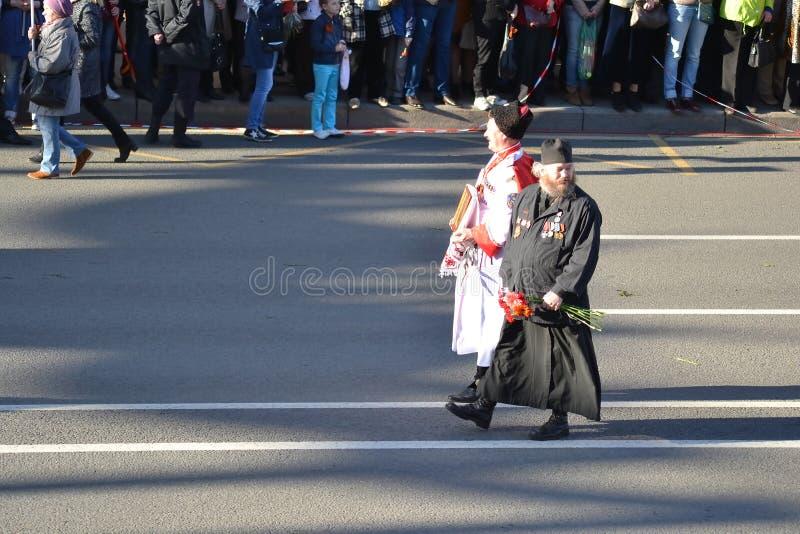El cosaco ruso y el sacerdote ortodoxo en la victoria desfilan foto de archivo