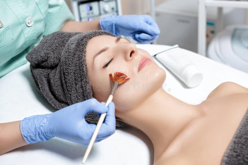 El cosmetólogo aplica la mascarilla con el cepillo a la mujer joven en balneario sa imagenes de archivo