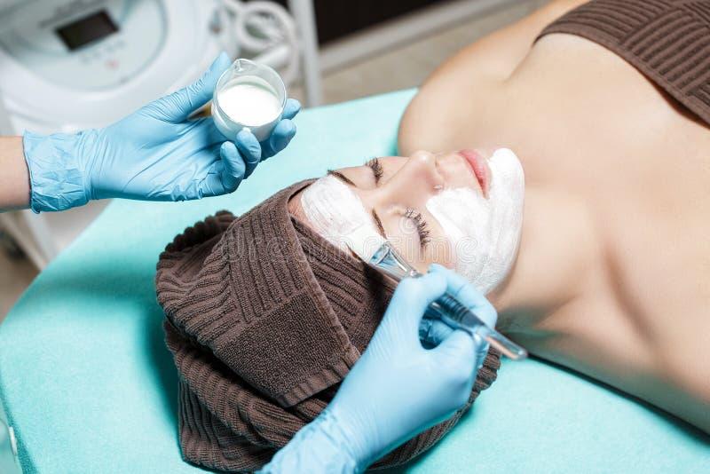 El cosmetólogo aplica la mascarilla en mujer joven hermosa en salón del balneario cuidado de piel cosmético del procedimiento Mic fotos de archivo libres de regalías