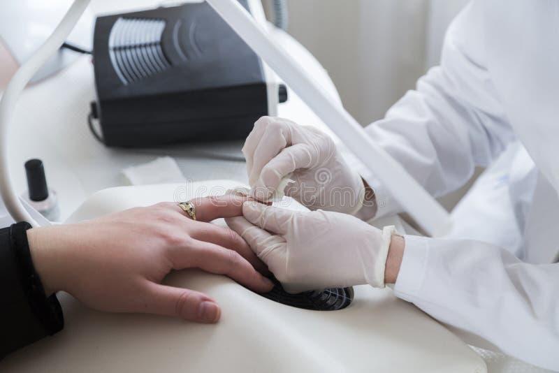 El cosmetólogo del Cosmetologist trata clavos del paciente con algodón fotografía de archivo