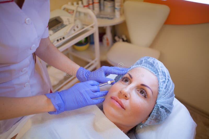 El cosmetólogo del doctor aumenta al paciente del labio una jeringuilla de la inyección foto de archivo libre de regalías