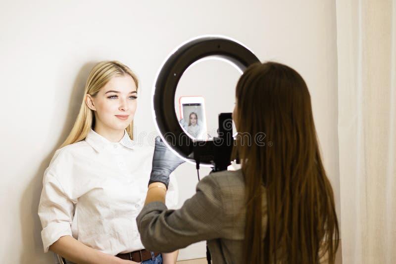 El cosmetólogo fotografía su trabajo sobre un teléfono móvil Dos muchachas en un salón de belleza Lámpara del anillo para los art imagenes de archivo