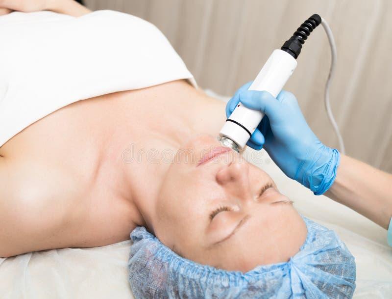 El cosmetólogo hace la RF-elevación a la mujer joven Los procedimientos cosméticos para la cara Tratamientos de la belleza en el  imágenes de archivo libres de regalías