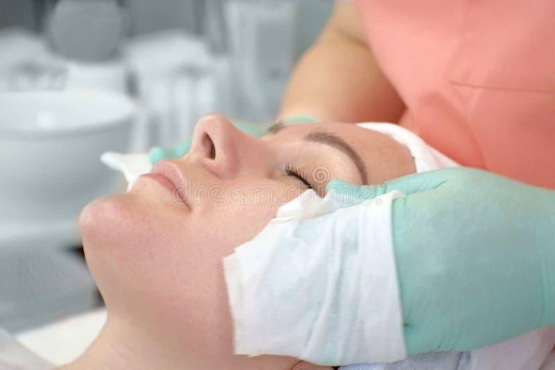 El cosmetólogo limpia la cara de una mujer Preparación de la cara antes del procedimiento cosmético Limpiamiento de la cara femen fotos de archivo libres de regalías
