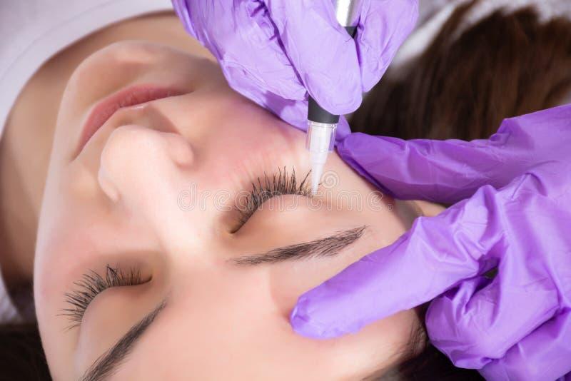 El cosmetólogo se prepara para aplicar el tatuaje permanente del lápiz de ojos en chica joven hermosa en estudio de la belleza fotos de archivo