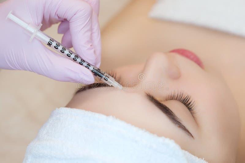 El cosmetologist del doctor hace el procedimiento facial de las inyecciones que rejuvenece para apretar y alisar arrugas imagenes de archivo