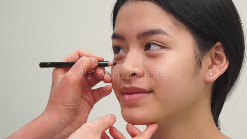 El Cosmetologist dibuja líneas debajo de ojo del ` s de la muchacha foto de archivo