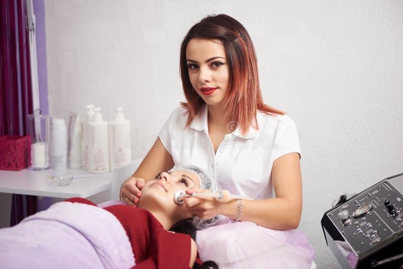 El cosmetologist femenino mira en la cámara mientras que hace el microdermabrasion a una mujer en un estudio blanco de la belleza imagen de archivo