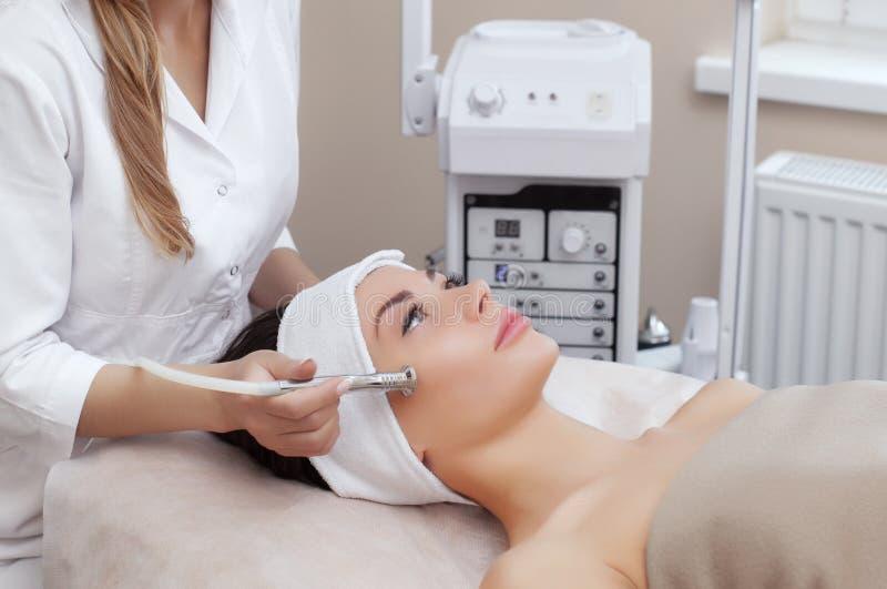 El cosmetologist hace el procedimiento Microdermabrasion de la piel facial de una mujer hermosa, joven fotos de archivo libres de regalías