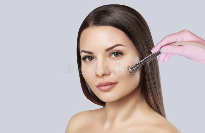 El cosmetologist hace el procedimiento Microdermabrasion de la piel facial de una mujer hermosa, joven en un salón de belleza El  imagen de archivo