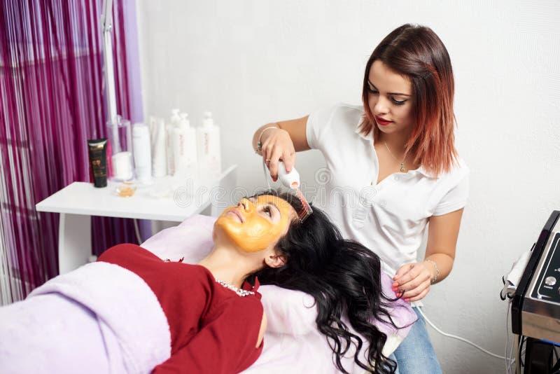 El Cosmetologist hace procedimiento terapia microcurrent en el pelo de hermoso imágenes de archivo libres de regalías