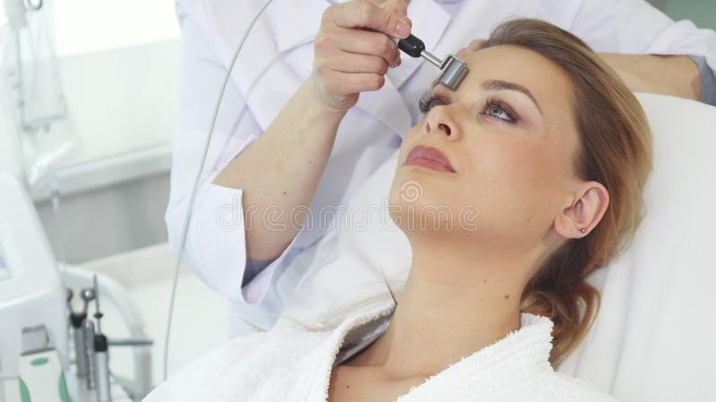 El Cosmetologist mueve el rodillo del iontophoresis a lo largo de la frente del ` s del cliente imagen de archivo