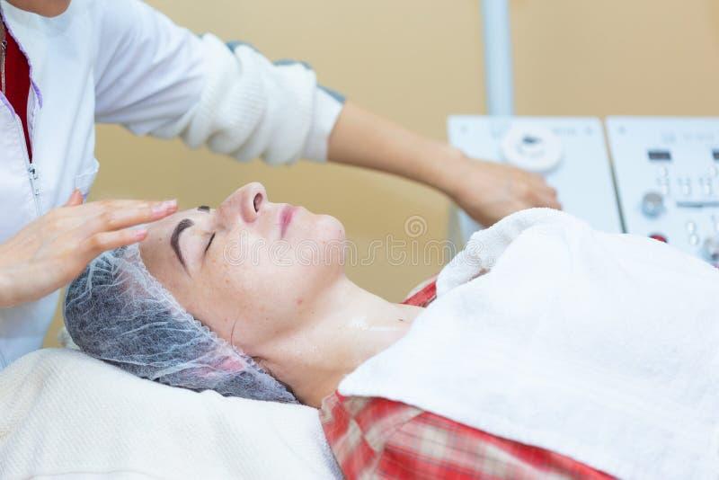El cosmetologist profesional hace procedimiento a la muchacha hermosa en gabinete de la cosmetolog?a imágenes de archivo libres de regalías