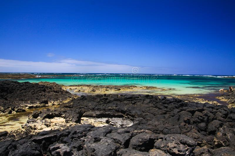 El Cotillo -法鲁del托斯顿:在黑火山岩和绿松石海洋天际北部费埃特文图拉岛之间的自然水池反对 库存图片