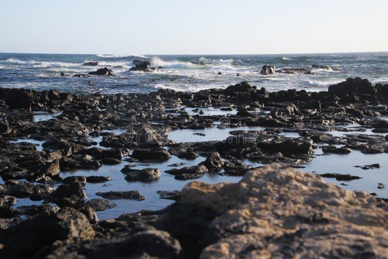 El Cotillo -法鲁del托斯顿:在黑火山岩的看法在有波浪的海洋 库存图片
