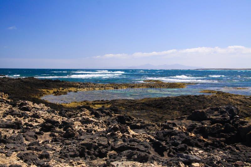EL Cotillo - Faro del Toston: Vista panorâmica no litoral áspero rochoso com lagoas e as associações naturais no norte de Fuertev fotos de stock royalty free