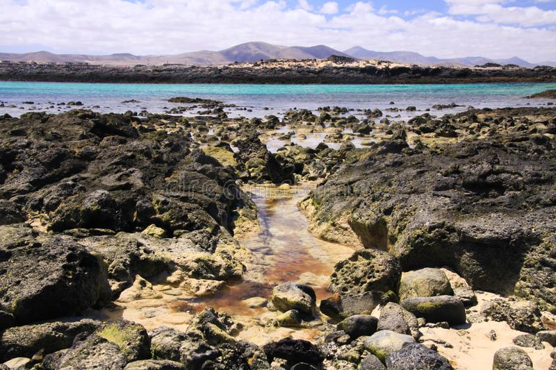 El Cotillo, North Fuerteventura: View over bright scattered stoneson beach in shallow water on turquoise lagoon of beach La Concha. Against deep blue sky stock photo