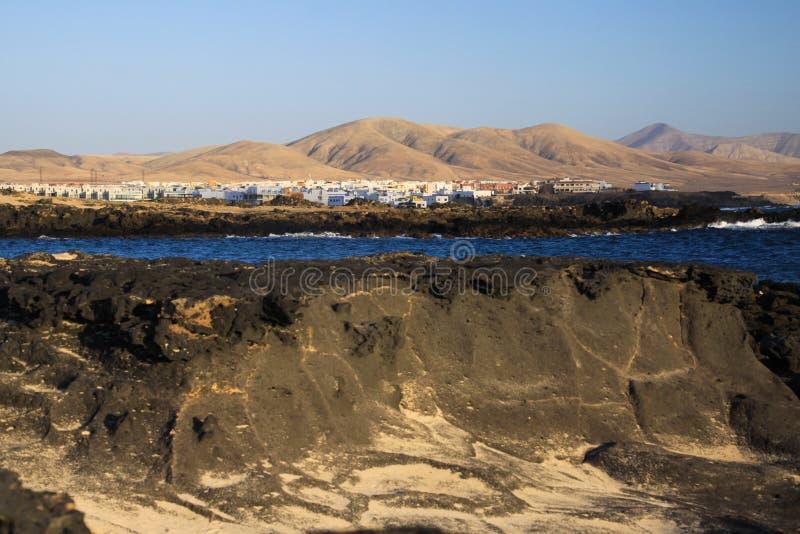 El Cotillo: Widok nad powulkanicznymi skałami i błękitną laguną na białej wiosce z suchą brązów wzgórzy tła północą Fuerteventura fotografia stock