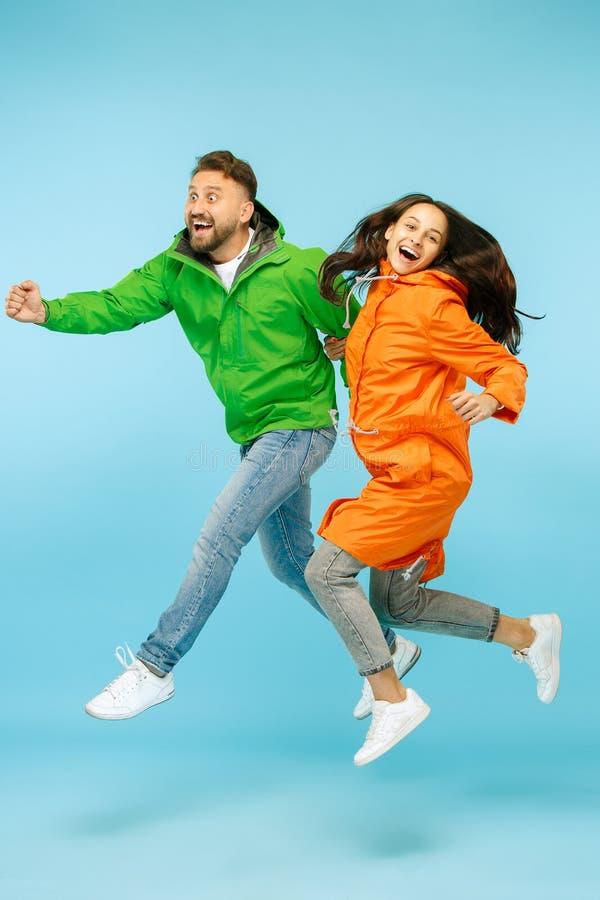 El couplel sorprendido jóvenes que presenta en el estudio en las chaquetas del otoño aisladas en azul foto de archivo