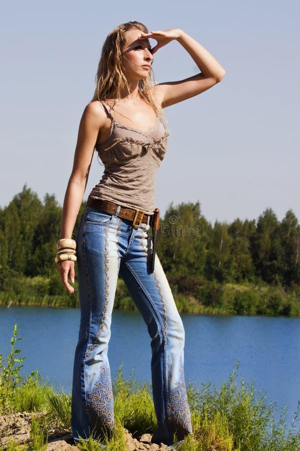 El Cowgirl en pantalones vaqueros se coloca en la batería foto de archivo