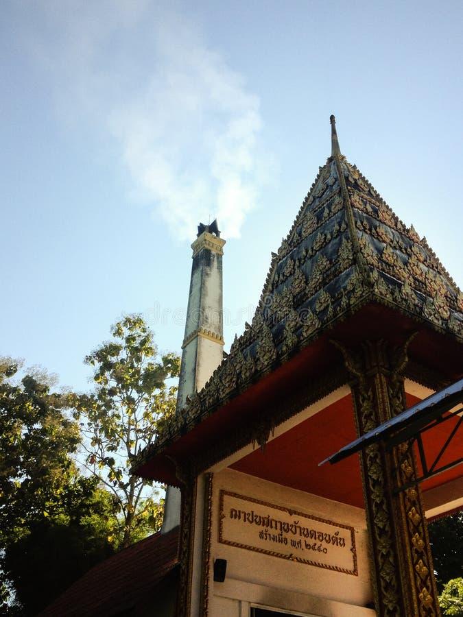 El crematorio con humo de incinera entierro en el templo de Tailandia el crematorio con el sol, el cielo azul y la nube Crematori imagen de archivo