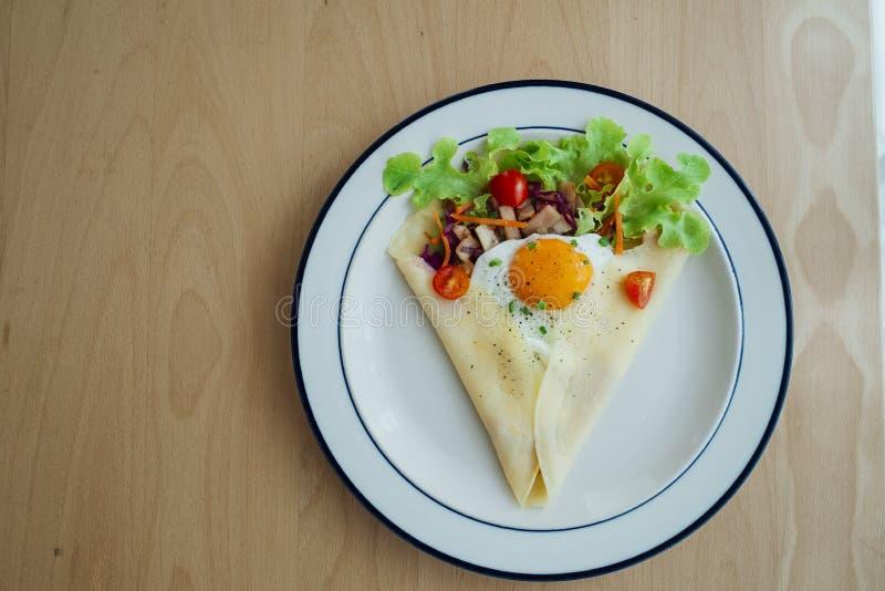 El crespón del jamón del pollo remató con el huevo y las verduras verdes imagenes de archivo
