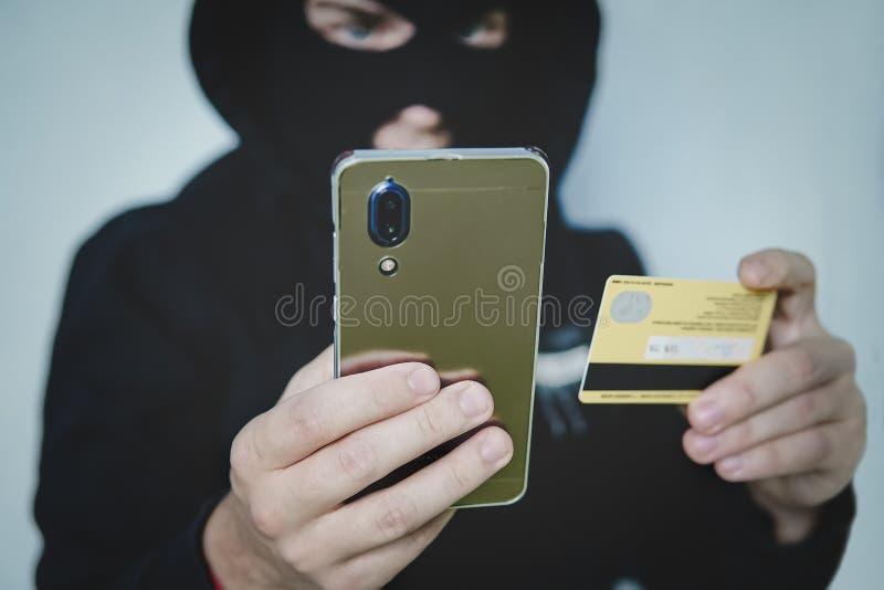 El criminal cibernético en pasamontañas incorpora la información de una cuenta bancaria personal Esquema fraudulento de la tarjet fotografía de archivo libre de regalías